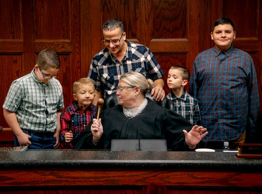 """Vanderburgh Superior Court Magistrate Renee Ferguson, center, offers her gavel to Eli Colacecchi, 6, to make his and his brothers' adoption """"official"""" during National Adoption Day Thursday morning, Nov. 11, 2019. J.T., 13, left, Zander, 8, second right, and Daniel, 14, all took the last name Colacecchi, the same as their new dad, Richard Colacecchi, top center, of Evansville."""