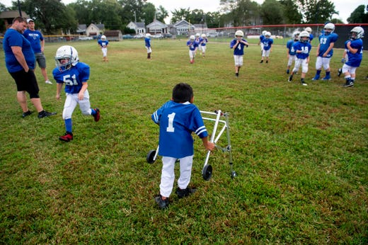 Andrew Marsh of Evansville, 8, watches the Evansville Junior Football League Colts warm up before they play the Broncos game at Howell Park in Evansville, Saturday afternoon, Sept. 14, 2019.