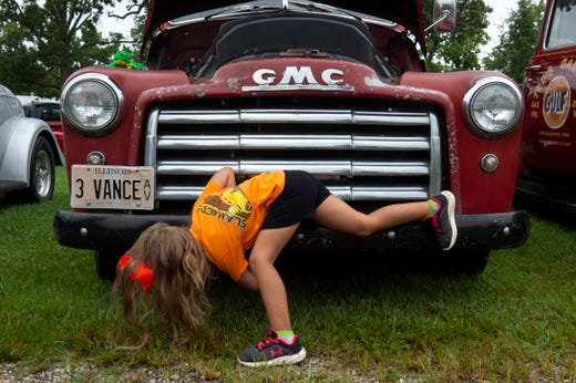 Faith Vance, 4, of Mount Vernon, Ill., looks underneath her father Quinton Vance's 1948 GMC at the 45th annual Frogs Follies held at Vanderburgh 4-H Center in Evansville, Friday afternoon, Aug. 23, 2019.