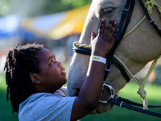 Jermarrius Pam meets Blondie, an 11-year-old Percheron draft cross horse, during Boom Fest held outside of the Stanley Hall Building in Evansville, Ind., Thursday, June 13, 2019. Blondie and Sergeant Tyrone Wood, not pictured, are members of the Evansville Police Department's mounted patrol.