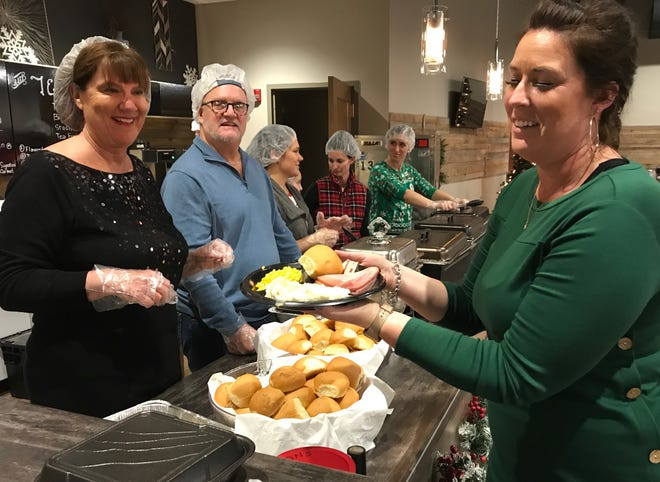 Young Life Green Bay volunteer Chelsea Faase, right, prepares to take a ham dinner to a guest at the Four Winds Free Community Christmas Dinner on Dec. 25, 2019, in Green Bay.