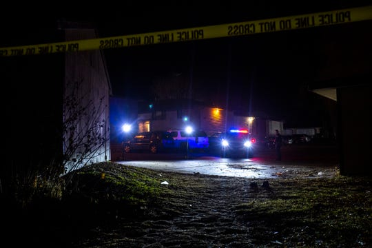 A Coralville police car illuminates a pair of shoes as officers investigate a scene of a shooting, early Thursday, Dec. 26, 2019, at an apartment complex on Boston Way in Coralville, Iowa.