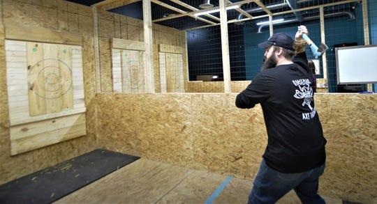Matthew Greear demonstrates how the ax throwing works on Dec. 20, 2019 in Jackson, Tenn.