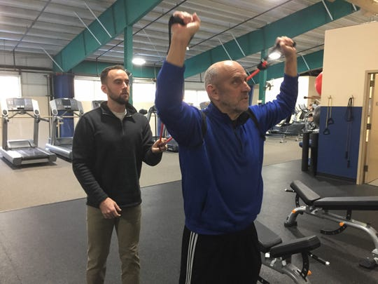 LEAP Health President Jeff Cremonte, left, helps his father, Tom Cremonte, do an exercise at the Hamburg Fitness Center, Thursday, Dec. 19, 2019. He will launch a free Facebook-based weight loss challenge on New Year's Day.
