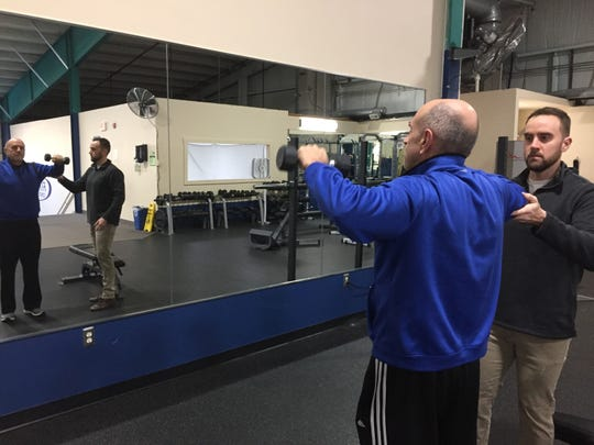 Jeff Cremonte, a physical therapist and president of LEAP Health, leads his father, Tom Cremonte, left, in a exercise at the Hamburg Fitness Center, Thursday, Dec. 19, 2019. He'll lead a free Facebook-based weight loss challenge.