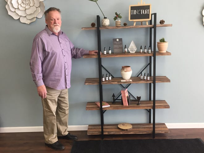 Bill Klug, manager at Your CBD Store, stands with a display of products.