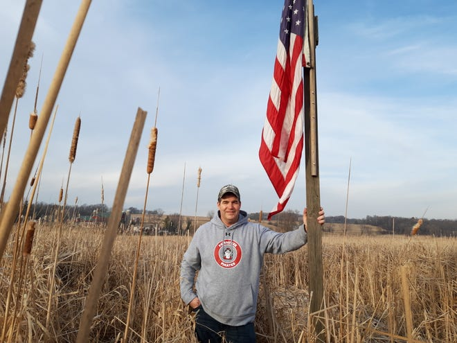 Scott Leffler of Pewaukee poses by an American flag he's put up in the middle of a marshy field on his property. The flag is visible on the north side of Highway 16 west of Sussex Street.