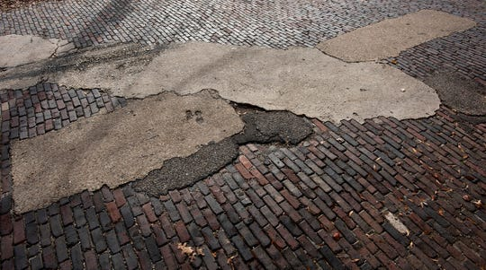 Asphalt and concrete patches in the brick lined block of Scott Street in downtown Montgomery, Ala., on Thursday December 26, 2019.