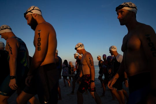 Fitness Challenge Triathlon competitors make their way to the starting line to begin their half-mile swim Sunday, June 2, 2019, in Naples.