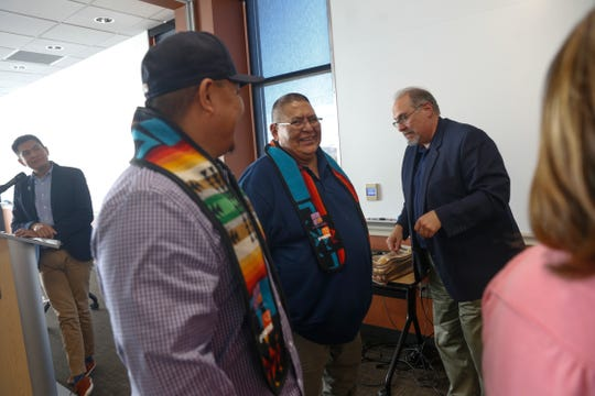 Byron Tsabetsaye, left, director of the Native American Center at San Juan College, announces the names of the 2018 PNM scholarship graduates during the April 24, 2018 graduation ceremony at the college's School of Energy in Farmington as Michael Benally, second to left, and Myron Charley receive their sashes and certificates.
