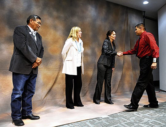 From left, Navajo Nation President Ben Shelly, PNM Resources Chairman, President and CEO Pat Vincent-Collawn and San Juan College President Toni Pendergrass, who is shaking hands with student Harrison Clark during the April 17, 2014 reception for the PNM Navajo Nation Workforce Training Program at the college's Henderson Fine Arts Center in Farmington.