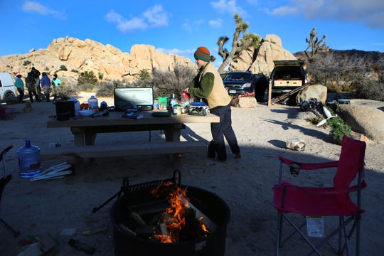 Camper Jasper Ohlson, 19, of San Diego keeps warm with a camp fire at Joshua Tree National Park in Joshua Tree, Calif., on Wednesday, December 25, 2019. Parts of Joshua Tree National Park could see snow fall starting overnight.