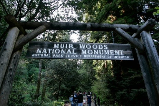 Visitors walk along a pathway near the entrance to the Muir Woods National Monument in Marin County, Calif.