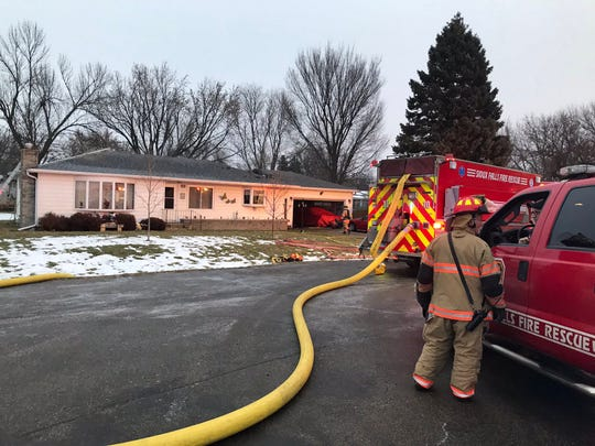 A Sioux Falls firefighter talks with Battalion Chief Jim Powers as crews monitor a house in the 6800 block of W. 10th Street for any other signs of flames following an early morning fire the day after Christmas, Dec. 26, 2019.
