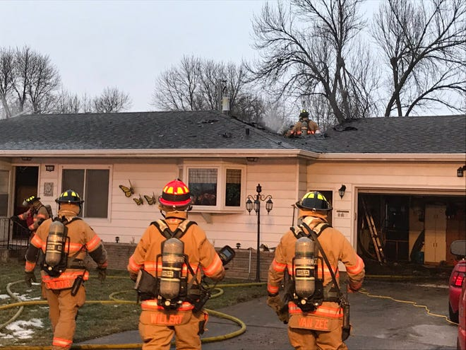 Sioux Falls firefighters work to knock down flames in the attack of a home in the 6800 block of W. 10th Street, the day after Christmas, Dec. 26, 2019.