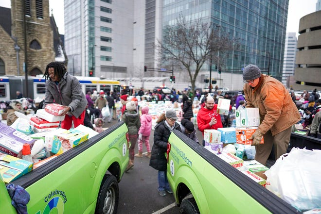 Volunteers help load donations onto trucks as residents of the Francis Drake Hotel apartment building were bussed to temporary shelters after the building caught a fire Wednesday, Dec. 25, 2019, in Minneapolis. Hundreds of people donated diapers, clothing and personal items after the early morning fire tore through the apartment building. The building mostly serves as temporary housing for homeless people.