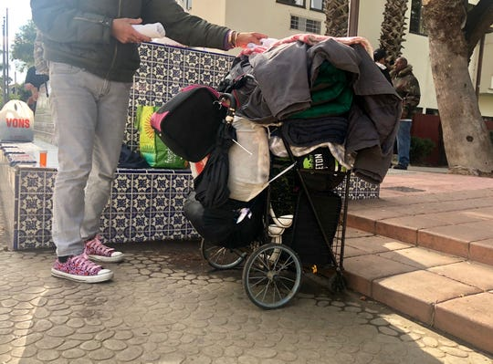 Melissa, who has been homeless for about eight years, reorganizes her sleeping bag, blankets and sleeping mat onto her cart on Dec. 26. 2019, after spending the night outside in the rain.