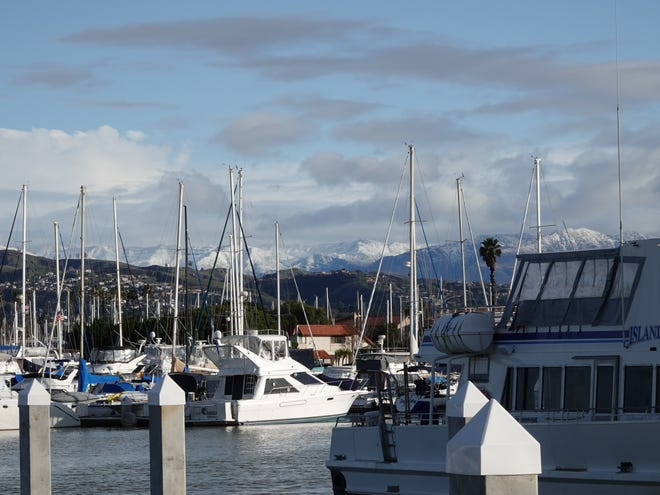 Snowy mountain tops show behind ship masts at Ventura Harbor in December 2019.