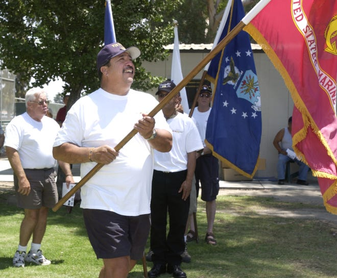 Vietnam Veteran Mike Garcia carries the United States Marine Corps flag during the Central Valley Vietnam Veterans ceremony at Tulare Veteran's Memorial Park on Saturday, June 2, 2007.