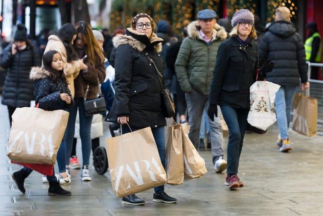 Shoppers walk down Oxford Street in London on Dec. 26.