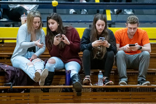 Bellevue fans take a break to check their phones at the Battle Creek Fieldhouse during the Chuck Turner Holiday Classic on Saturday, Dec. 27, 2019.