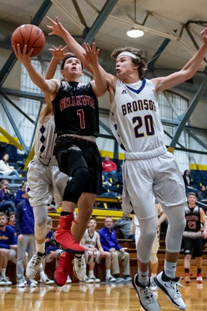Bellevue's Grant Morgan (1) goes for the layup over Bronson's Reagan Mayer (20) at the Battle Creek Fieldhouse during the Chuck Turner Holiday Classic on Saturday, Dec. 27, 2019.
