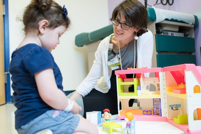 Child Life Specialist Jennifer Eddy, BA, CCLS, speaks with a pediatric patient at the UVM Children's Hospital.