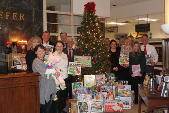 Gebhardt & Kiefer employees present 135 toys and games to Salvation Army Lt. Amanda Boynton (fourth from left) for distribution to area families.