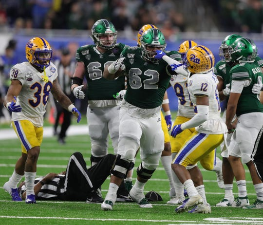 Eastern Michigan Eagles offensive lineman Sidy Sow (62) and Pittsburgh Panthers defensive back Paris Ford (12) mix it up during second half action of the Quick Lane Bowl on Thursday, Dec. 26, 2019, at Ford Field in Detroit.