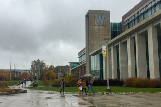 Students walk past Sangren Hall on Western Michigan University's campus on a rainy day in late October, 2019.