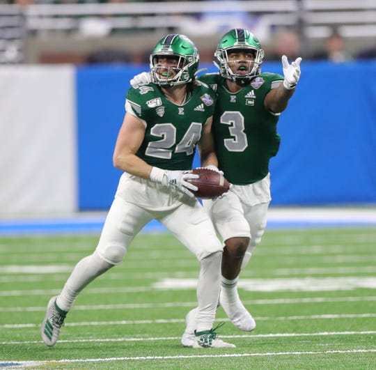 Eastern Michigan Eagles defensive backs Brody Hoying (24) and Vince Calhoun celebrate after recovering a fumble by Pittsburgh during the first half of the Quick Lane Bowl, Thursday, Dec. 26, 2019 at Ford Field in Detroit.