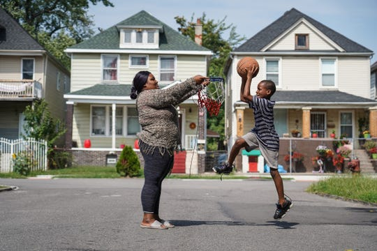 """TayJahnae Stanley of Detroit holds a basketball hoop for her cousin AJ Mason as he comes in for a dunk while she played the roll of the basketball post on Carkdale St. in Southwest Detroit on Friday, September 13, 2019. """"Sometimes the ball will hit you in the face or hit you in the hand. It hurts,"""" Stanley said, while helping her cousin who hopes to one day play point guard for the Detroit Pistons. """"It's his passion. He loves ball. I love making my little cousins happy."""""""