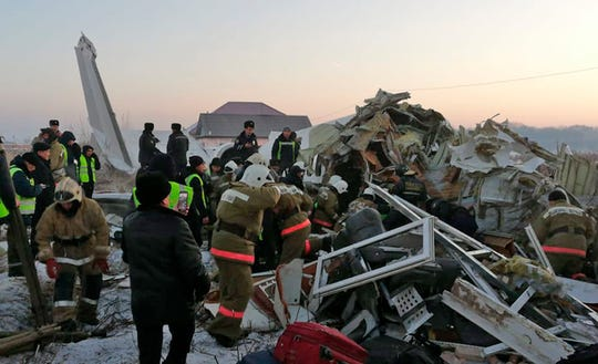 Police and rescuers work on the side of a plane crash near Almaty International Airport, outside Almaty, Kazakhstan, Friday, Dec. 27, 2019.