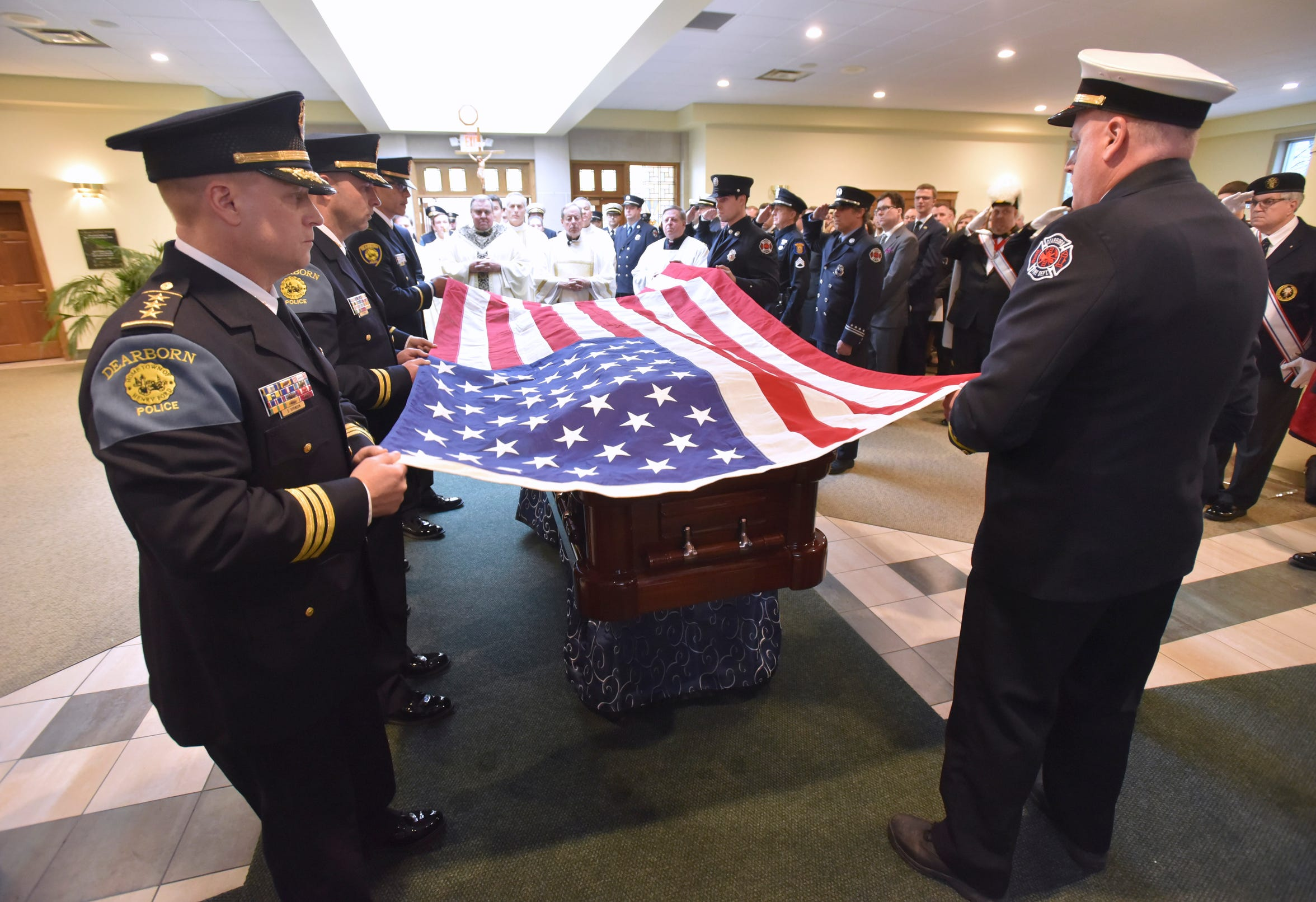 Dearborn police officers and fire fighters drape the United States flag over John Dingell's casket during a mass for the former U.S. Congressman February 12, 2019, at the Church of the Divine Child in Dearborn. Dingell, a Michigan Democrat who served in the U.S. House from 1955 to 2015, and was the longest-serving member of Congress in American history, died Feb. 7,2019 at the age of 92.