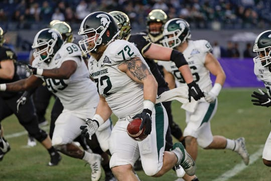 Michigan State's Mike Panasiuk runs back an interception for a touchdown during the first half.