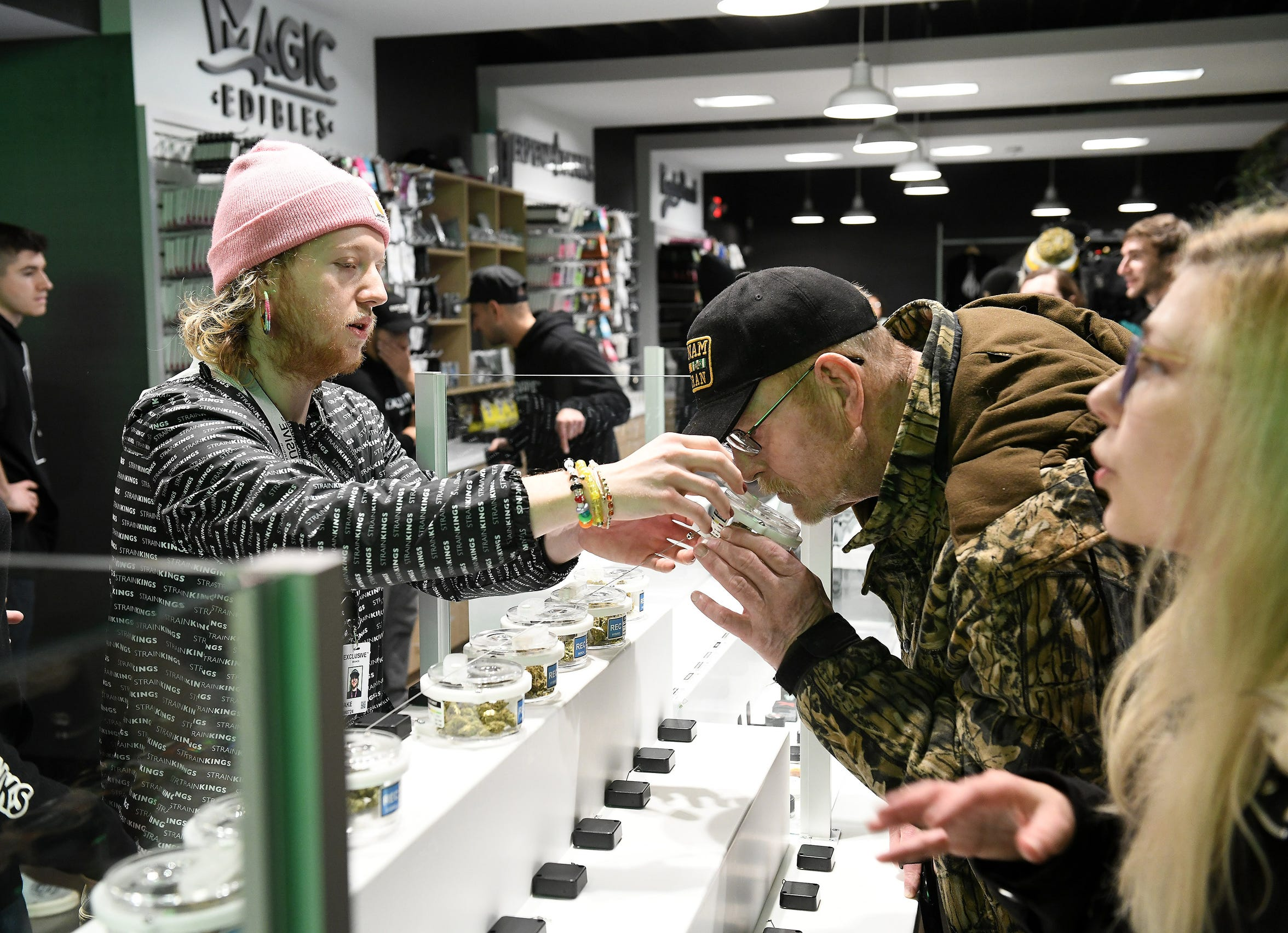 Tender Jacob Samways, left, lets Gregg Etzel, 67, of Dundee smell some marijuana flowers during the first day of sales of recreational marijuana at Exclusive Provisioning Center in Ann Arbor, Mich. on Dec. 1, 2019.