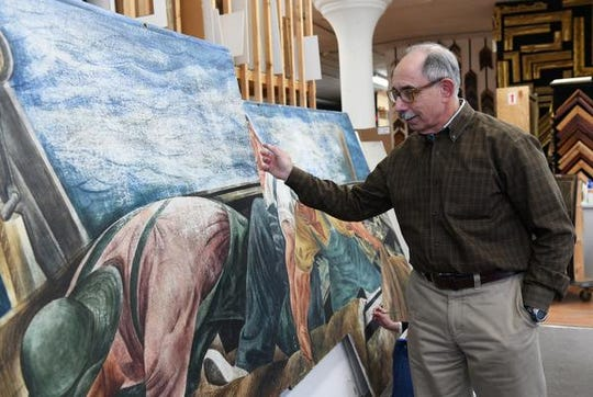 Detroit art conservator Kenneth Katz notes areas of significant damage to the Zoltan Sepeshy mural, where an earlier, botched restoration scraped the egg-tempera paint right off.