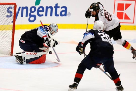 United States goalkeeper Dustin Wolf, left, makes a save on Germany's Lukas Reichel with Arthur Kaliyev back on the play on Friday at the world junior championship.