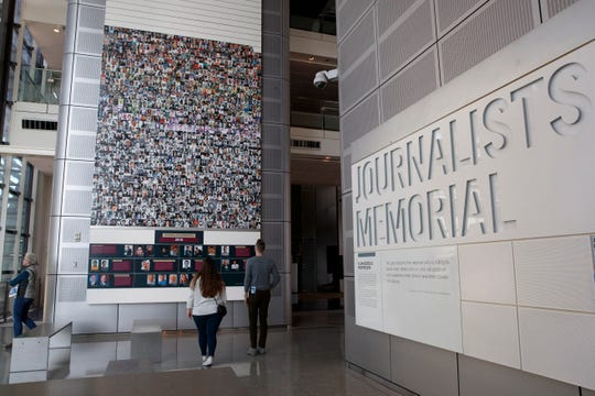 People visit the journalists memorial at the Newseum, Friday, Dec. 20, 2019, in Washington.