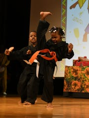 Alkebu-Lan Village students Krysten (cq) Barden, right, and Ezrael Rhymes perform a demonstration at the first day of Kwanzaa celebration at the Charles H. Wright Museum of African American History in Detroit.