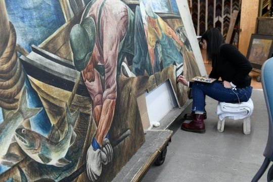 """Loredana Zanchi works on restoring a mural by Zoltan Sepeshy at Conservation & Museum Services in Detroit.  The mural, """"Hauling in the Net,"""" will return to the Mormon Print Shop Museum on Beaver Island once it's finished this spring."""