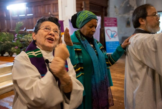 The Rev. Maria Santiviago, left, signs the sermon for deaf worshippers at Holyrood Episcopal Church-Iglesia Santa Cruz in the Washington Heights neighborhood in New York City, Sunday, Dec. 22, 2019.