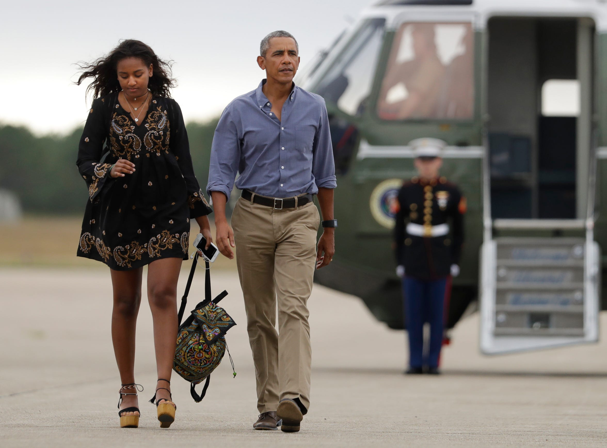 President Barack Obama and daughter Sasha Obama, walk on the tarmac to board Air Force One at Air Station Cape Cod in Mass., Sunday, Aug. 21, 2016. Sasha enrolled in the University of Michigan last fall.