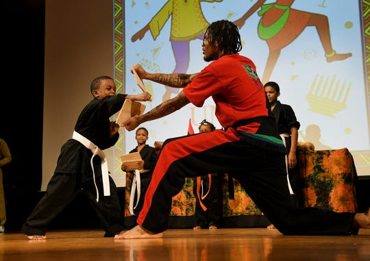 Alkebu-Lan Village martial arts instructor Kristian Barden, right, holds the board being broken by Ishmael Rhymes during a demonstration at the first day of Kwanzaa celebration at the Charles H. Wright Museum of African American History in Detroit .