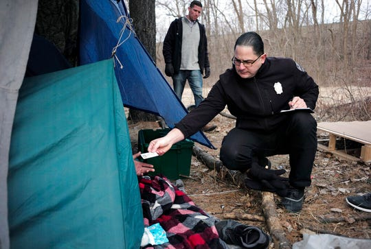 Worcester Police officer Angel Rivera, right, returns a license to an unidentified man as Rivera asks if he has been tested for Hepatitis A at the entrance to a tent where the man spent the night in a wooded area, in Worcester, Mass. At background center is Dan Cahill, City of Worcester sanitary inspector. The city was hit hard when recent hepatitis A outbreaks across the country started sickening and killing homeless people and illicit drug users.