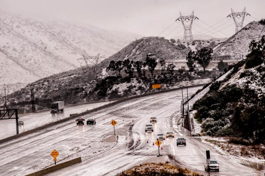 Vehicles are diverted off the northbound 15 Freeway to Kenwood Ave. on-ramp as Cajon Pass is shut down due to heavy snowfall in San Bernardino, Calif., on Thursday.