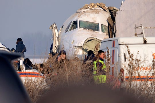 Police stand guard as rescuers assist on the site of a plane crashed near Almaty International Airport, outside Almaty, Kazakhstan on Friday. The Kazakhstan plane with 98 people aboard crashed shortly after takeoff early Friday.