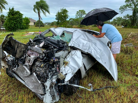 Jim Durkin of Cape Coral takes a closer look at his heavily damaged car that was thrown across the street from the home he was staying at. Family, Friends and neighbors picked up the pieces of their NW Cape neighborhood Saturday morning after a Tornado hit near the 2000 block of Van Buren Parkway, October 19, 2019.