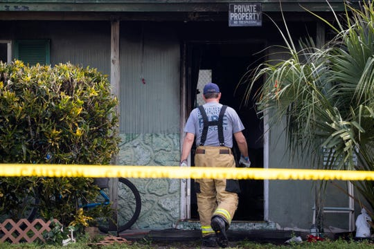 A San Carlos Park fire fighter enters a house that burned early Friday morning, Dec. 27, 2019, in Fort Myers.
