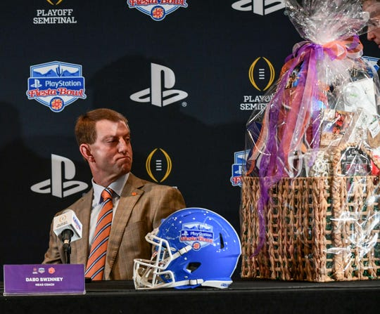 Clemson Head Coach Dabo Swinney looks at a gift basket before the Fiesta Bowl coaches press conference in Scottsdale, Arizona Friday December 27, 2019.